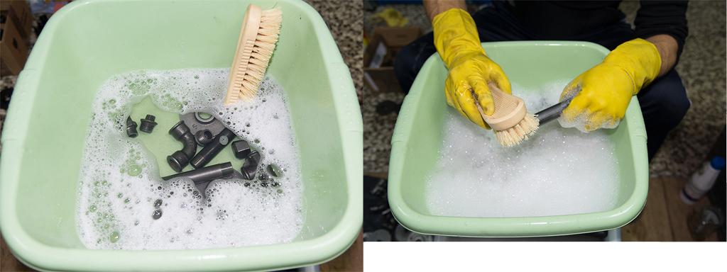 Metalowe elementy w misce z wodą w trakcie odtłuszczania